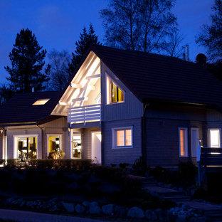 Diseño de fachada gris, escandinava, grande, a niveles, con revestimiento de madera y tejado a dos aguas