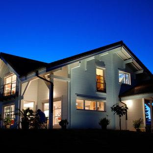 Aménagement d'une grande façade en bois blanche contemporaine à un étage avec un toit à deux pans.