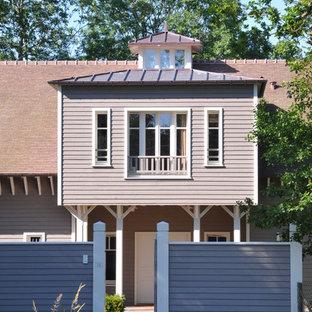 Réalisation d'une très grande façade de maison grise craftsman à un étage avec un toit à deux pans et un toit en tuile.