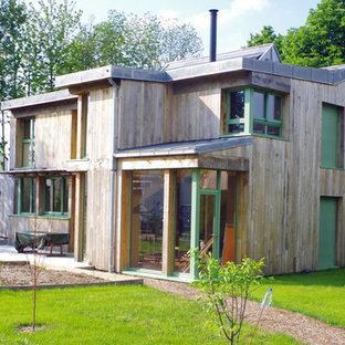 Cette image montre une façade de maison marron design à un étage avec un toit en métal.