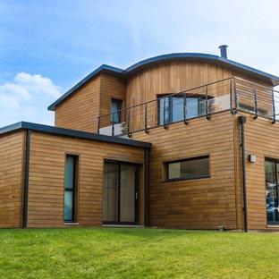 Cette photo montre une grande façade de maison marron moderne à un étage.