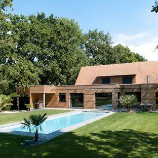 Aménagement d'une façade de maison marron contemporaine de taille moyenne et à un étage avec un toit plat et un toit en tuile.