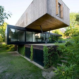 Foto della facciata di una casa contemporanea a tre piani con rivestimento in legno e tetto piano