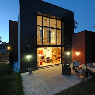Cette image montre une façade de maison grise design de taille moyenne et à un étage avec un toit plat.