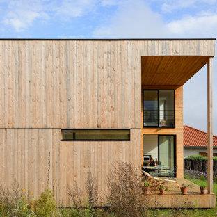 Exemple d'une grand façade en bois tendance à un étage avec un toit plat.