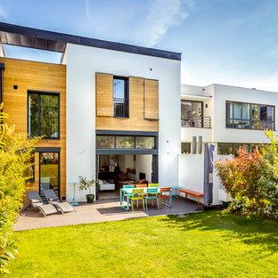 Exemple d'une façade de maison multicolore tendance à un étage avec un revêtement mixte et un toit plat.