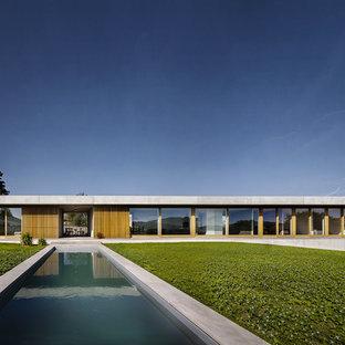 Cette photo montre une grand façade en béton grise tendance de plain-pied avec un toit plat.