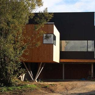 Idée de décoration pour une façade de maison noire design de taille moyenne et à un étage avec un toit plat.
