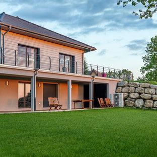Cette image montre une façade de maison beige traditionnelle de taille moyenne et à un étage avec un toit à quatre pans.