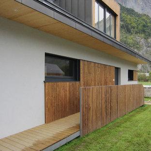Idées déco pour une façade de maison blanche moderne de taille moyenne et à un étage avec un revêtement mixte et un toit à deux pans.