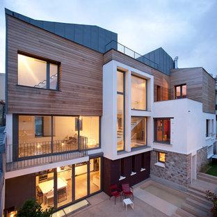 Cette photo montre une grand façade de maison tendance à deux étages et plus avec un revêtement mixte et un toit plat.