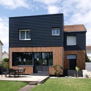 На фото: двухэтажный, деревянный, черный частный загородный дом среднего размера в современном стиле с крышей-бабочкой и черепичной крышей