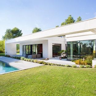 Inspiration pour une très grand façade en béton blanche minimaliste de plain-pied avec un toit plat.