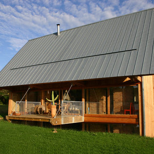 Cette image montre une façade en bois marron rustique de taille moyenne et à un étage avec un toit à deux pans.