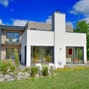 Idée de décoration pour une façade de maison blanche design à un étage avec un toit plat.
