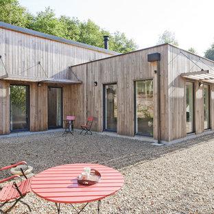 Cette photo montre une façade en bois marron tendance de taille moyenne et de plain-pied avec un toit plat.
