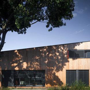 Idées déco pour une façade en bois marron contemporaine de taille moyenne et à un étage avec un toit en appentis.
