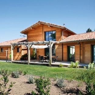 Réalisation d'une façade en bois marron chalet de taille moyenne et à un étage avec un toit à deux pans.