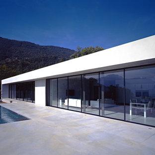Idée de décoration pour une grande façade en verre blanche minimaliste de plain-pied avec un toit plat.