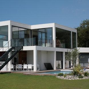 Exemple d'une grand façade de maison blanche moderne à un étage avec un toit plat et un toit mixte.