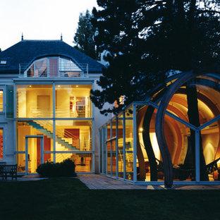 Inspiration pour une grande façade en verre blanche design à deux étages et plus avec un toit à quatre pans.