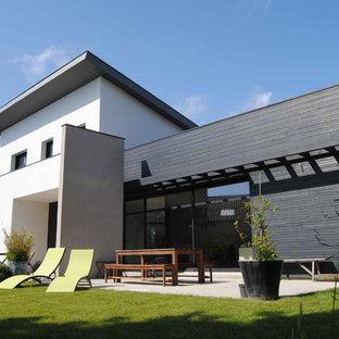 Cette photo montre une grand façade de maison blanche tendance à un étage avec un toit plat.