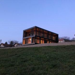 Foto de fachada de casa negra, contemporánea, de tamaño medio, de dos plantas, con revestimiento de madera, tejado plano y techo verde