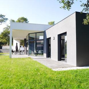 Aménagement d'une façade de maison grise contemporaine de taille moyenne et de plain-pied avec un revêtement mixte et un toit plat.