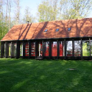 Réalisation d'une façade en verre design de taille moyenne et à un étage avec un toit à deux pans.