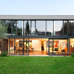 Inspiration pour une grand façade de maison grise minimaliste à un étage avec un toit plat et un toit en métal.
