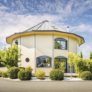 Idée de décoration pour une grand façade de maison beige design à un étage avec un toit à quatre pans et un toit en métal.