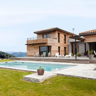 Idée de décoration pour une grand façade en bois marron design à un étage avec un toit à quatre pans.