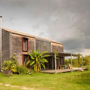 Imagen de fachada tropical, de tamaño medio, con tejado a dos aguas y revestimiento de madera