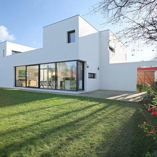 Idée de décoration pour une façade de maison blanche design à un étage avec un revêtement en stuc et un toit plat.