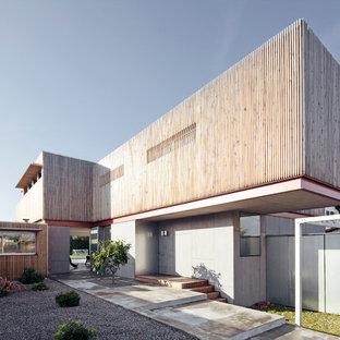 Inspiration pour une grande façade de maison grise design à un étage avec un toit plat et un revêtement mixte.