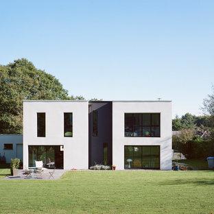 Idée de décoration pour une façade de maison blanche minimaliste de taille moyenne et à un étage avec un toit plat.