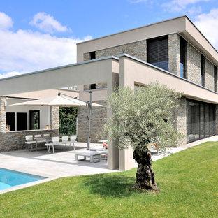 Idées déco pour une façade de maison beige contemporaine à un étage avec un toit plat.