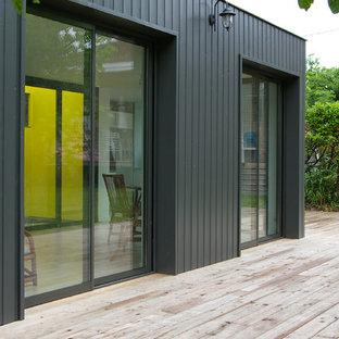 Réalisation d'une façade en bois noire design de taille moyenne et de plain-pied avec un toit plat.