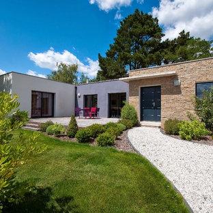 Cette photo montre une façade en pierre beige tendance de taille moyenne et de plain-pied avec un toit plat.