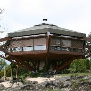 Cette image montre une grande façade de maison marron design à un étage avec un revêtement mixte et un toit à quatre pans.