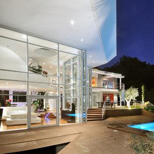 Cette photo montre une très grand façade en verre blanche tendance à un étage avec un toit plat.