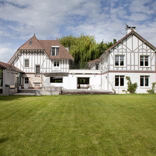 Idées déco pour une façade de maison classique avec un toit à croupette.