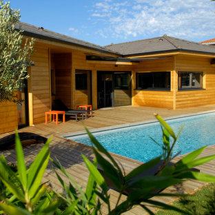 Cette photo montre une façade en bois marron tendance de taille moyenne et de plain-pied avec un toit à quatre pans.