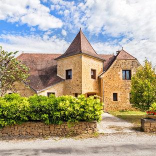 Idées déco pour une façade en pierre beige classique de taille moyenne et à un étage avec un toit à croupette.
