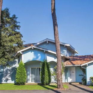 Inspiration pour une façade en bois bleue traditionnelle de taille moyenne et à un étage avec un toit à deux pans.