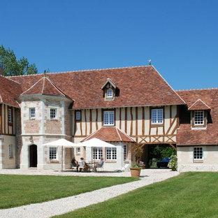 Idée de décoration pour une grande façade de maison beige champêtre à deux étages et plus avec un revêtement mixte et un toit à quatre pans.