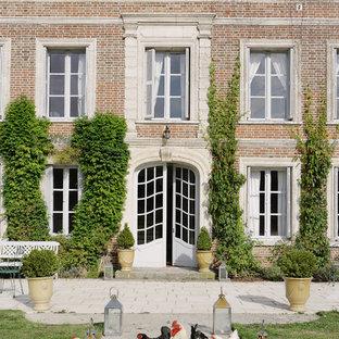 Réalisation d'une grand façade en brique marron tradition à deux étages et plus avec un toit à deux pans.