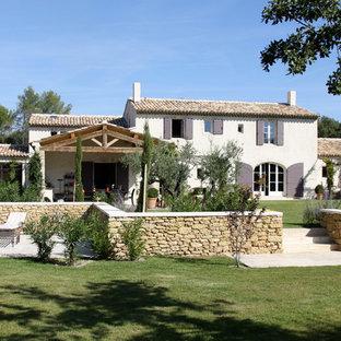 Aménagement d'une grande façade de maison blanche méditerranéenne à un étage avec un toit à deux pans.