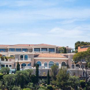Idée de décoration pour une très grande façade de maison méditerranéenne avec un toit à quatre pans.
