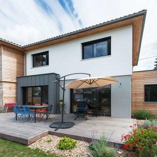 Inspiration pour une façade de maison double multicolore design à un étage avec un revêtement mixte, un toit plat et un toit en tuile.